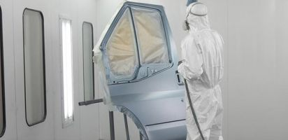 Man spraypainting a car door in a spray booth. It is a light metallic blue colour